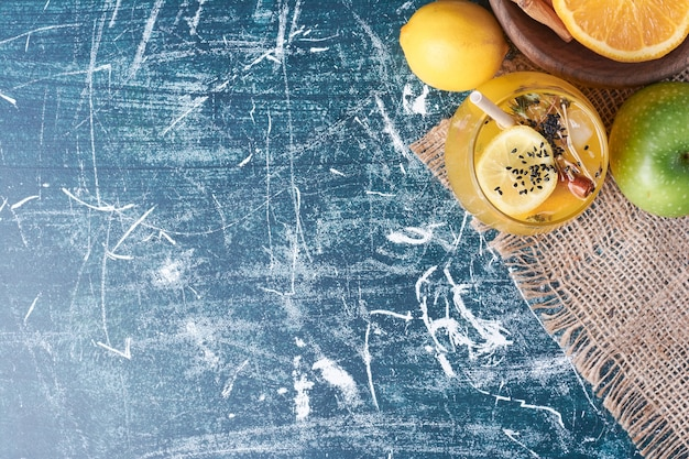 Лимоны с чашкой напитка на синем.