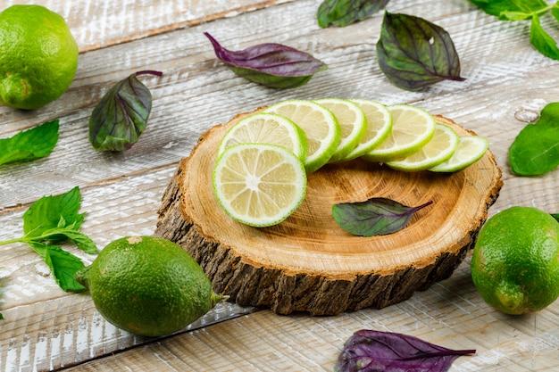 木製とまな板、ハイアングルでバジルとレモンの葉します。