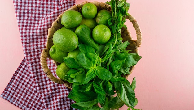 Lemons with basil leaves in a wicker basket on pink and kitchen towel, flat lay.