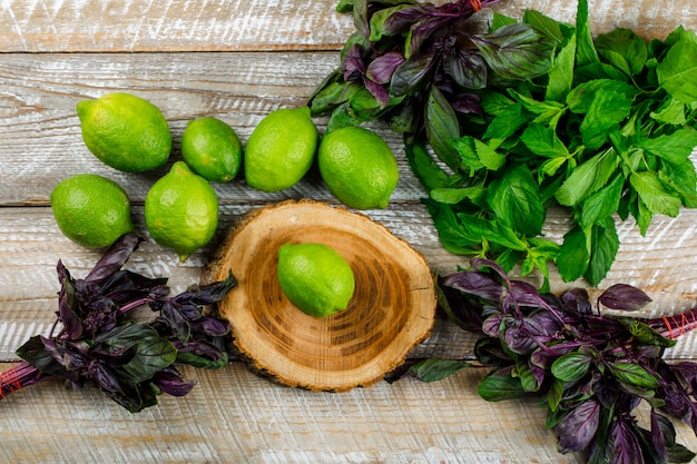 Lemons with basil leaves on wooden and cutting board, flat lay.