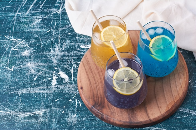 Lemons with colorful cups of drink on blue.