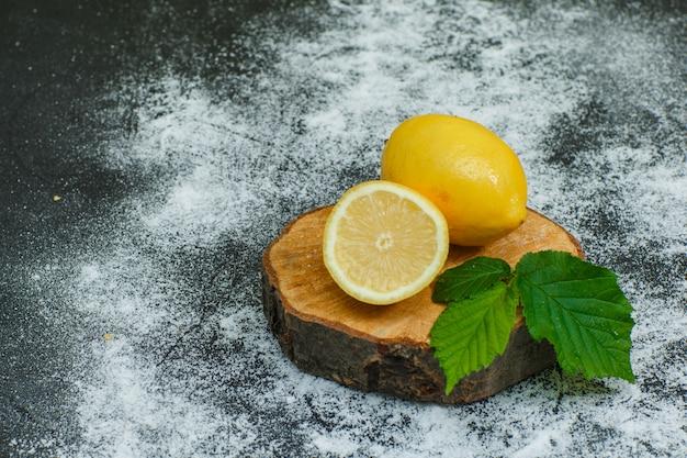 レモンの葉と乾燥シナモンハイアングルウッドスライスと暗い