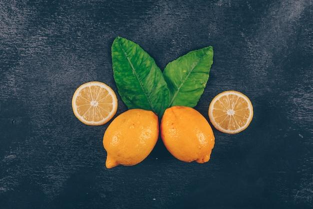 レモンの葉とスライスの黒いテクスチャ背景の上面図