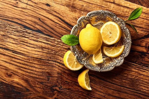 オークの木製テーブルの上の葉でレモン。デザインまたはテキスト用のスペースをコピーします。果物のトップビュー。