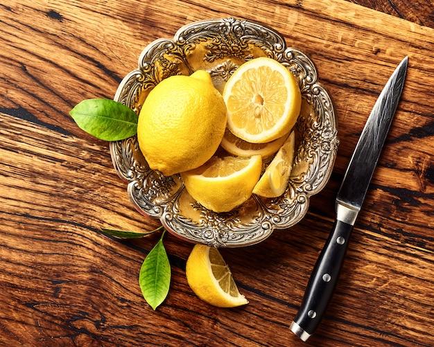 オークの木製テーブルの上の葉でレモン。ナイフで果物の平面図です。