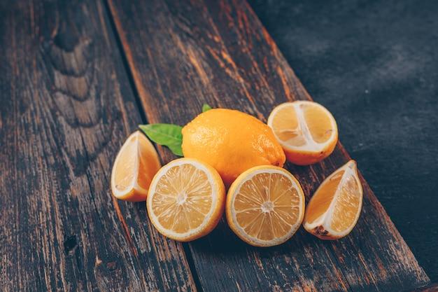 Limoni con la vista dell'angolo alto delle fette e delle foglie su un vassoio di legno e su un fondo strutturato nero
