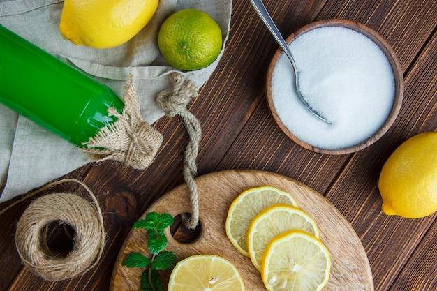 Лимоны с лаймом, зеленью, напитком, разделочной доской, солью, ниткой, плоско уложить на деревянное и кухонное полотенце