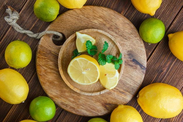 Lemons with limes, leaves in a wooden plate on wooden and cutting board, flat lay.