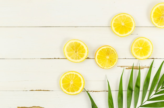 Lemons with palm leaf on table