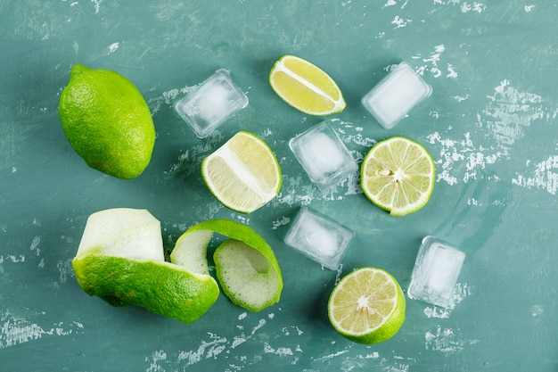 Lemons with peel, ice cubes flat lay on a plaster