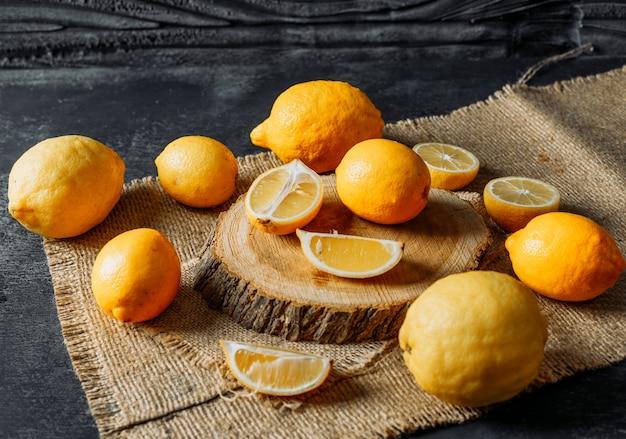 Limoni con la vista dell'angolo alto delle fette su una fetta di legno, su un panno e su un fondo scuro