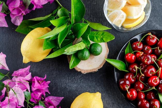 レモンスライス、葉、花、さくらんぼ、灰色の表面、上面に木の板