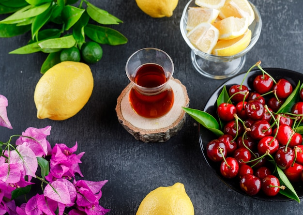 Lemons with slices, leaves, flowers and glass of tea
