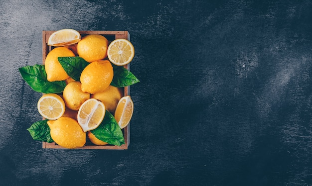 Lemons with slices and leaves in a wooden box on black textured background, top view. copy space for text