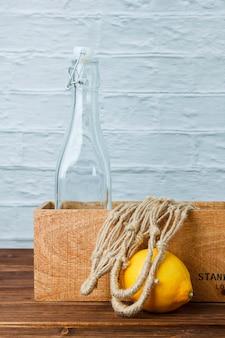 Лимоны с деревянным ящиком и видом сбоку веревки на деревянной и белой поверхности пространства для текста