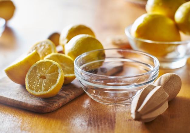 ジュースにして搾り出す準備ができている木製のリーマーが付いているレモン