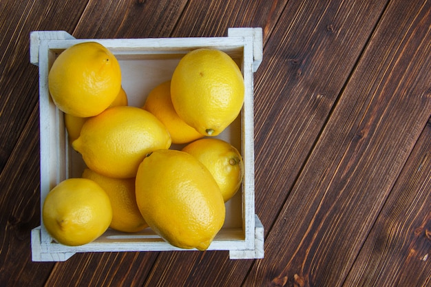Lemons in a wooden box flat lay on a wooden table