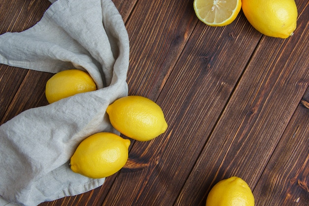 Limoni su legno e asciugamano da cucina, piatto laici.