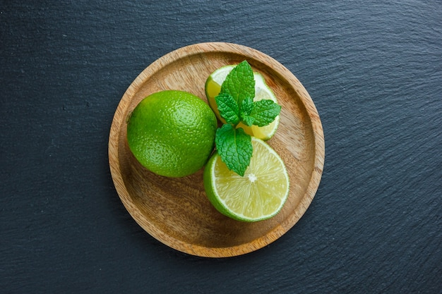 Lemons in a wooden plate on a dark stone surface. top view. copy space for text
