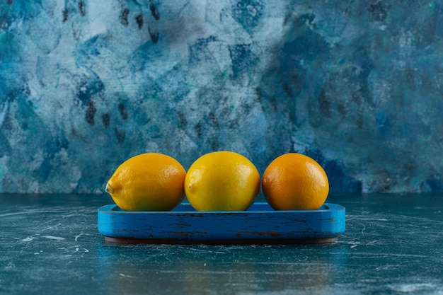 Lemons on a wooden plate , on the marble table.