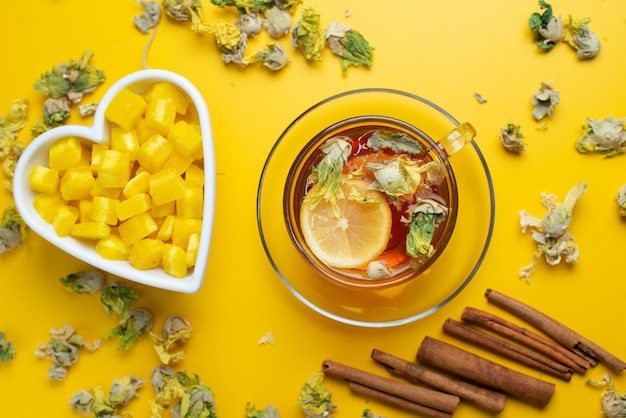 Lemony tea with dried herbs, sugar cubes, cinnamon sticks in a cup on yellow surface, flat lay.
