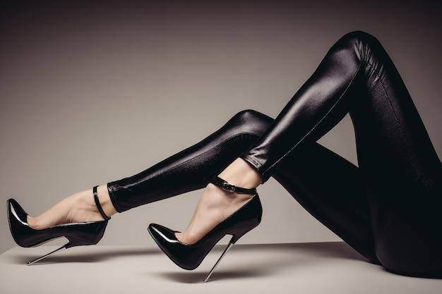 스판덱스 캣 수트를 입은 여성 다리와 매우 하이힐이 달린 페티쉬 신발. bdsm 테마.