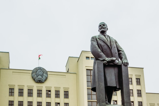 Lenin monument on the background of the coat of arms of belarus