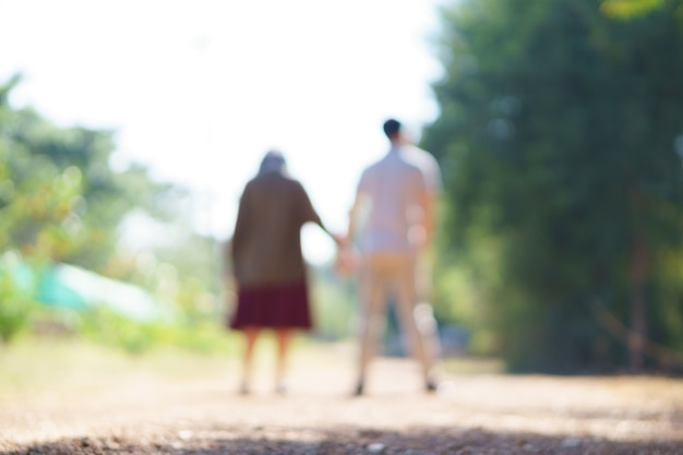 Lens blurred back view of young asian couple holding hands