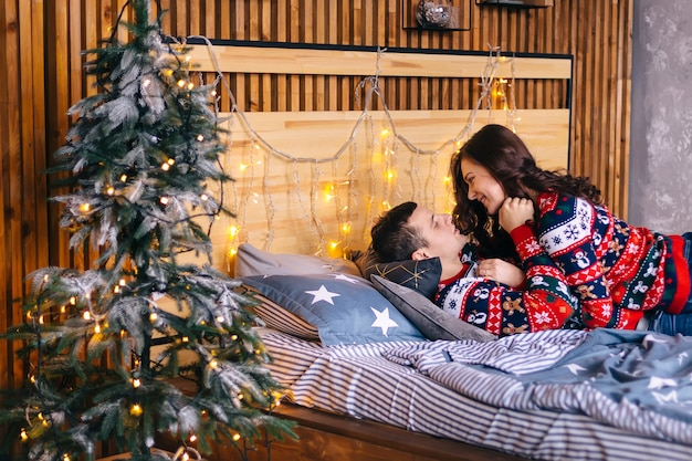 レンズフレア。男と女はベッドでくすぐります。ベッドの近くに花輪を持つクリスマスツリー。楽しんで。