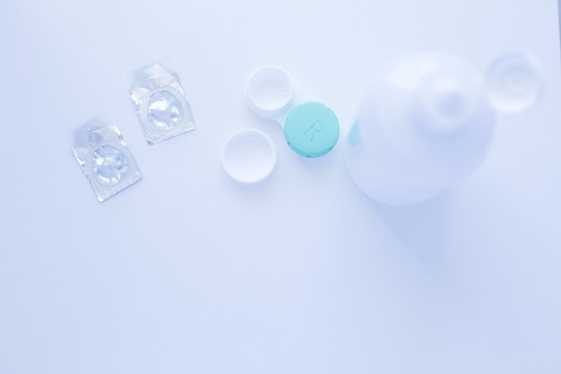 A lens remover a lens storage container and two contact lenses lie on top of the photo on a white ba...