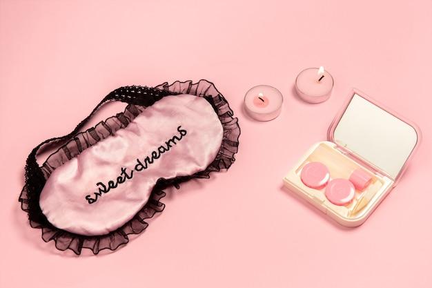 Линзы в футляре с зеркалом, маска для сна, свечи. монохромная стильная и модная композиция в розовом цвете на стене. вид сверху, плоская планировка.