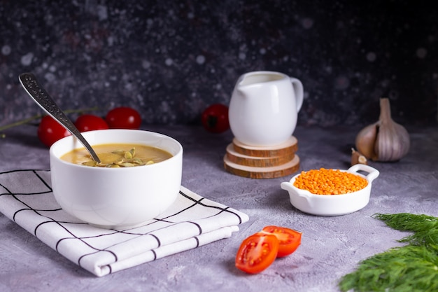 灰色の表面に木製のスタンドにクリーマーと白い皿にディルとレンズ豆とカボチャのクリームスープ