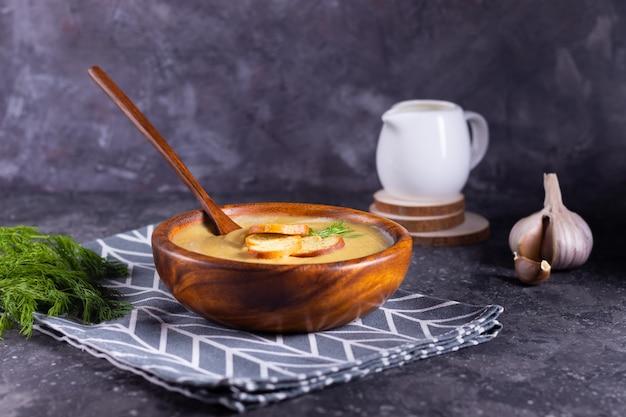 レンズ豆とカボチャのクリームスープ、木製のスタンドにクリーマーと木のスプーンで木の板にディルを添えて