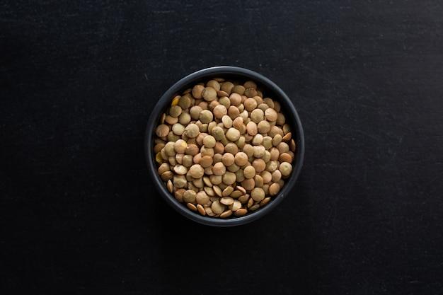 Lentil in bowl on dark background. mockup. top view