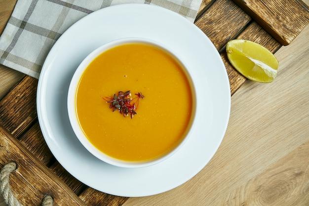白いボウルの木製トレイにレモンのスライスとレンズ豆のクリームスープ。健康的なビーガンフード。緑に行く。