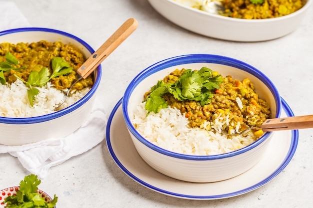 Lentil curry with rice, indian cuisine, tarka dal, white background. vegan food.
