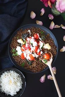 토마토와 구운 시금치, 요구르트와 타히니 소스를 곁들인 렌즈콩 요리