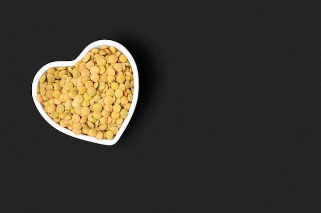 黒い背景にハート型のボウルにレンズ豆の穀物