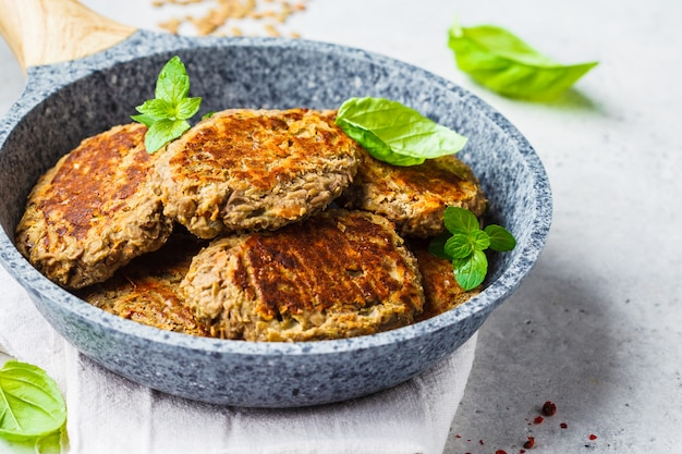 Lentil patties in gray frying pan. healthy vegan food concept.