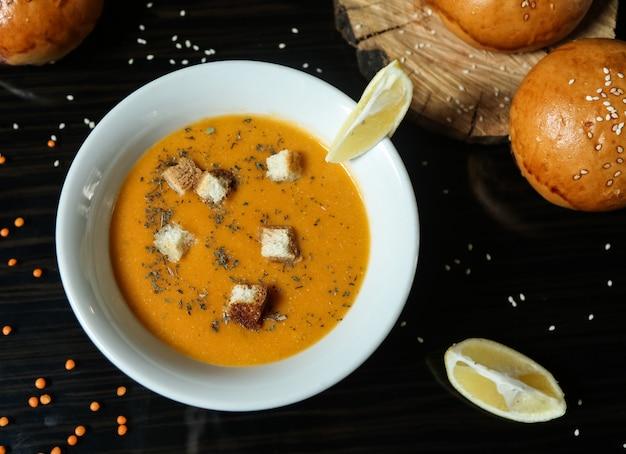 Lentil soup in bowl mint lemon crackers top view