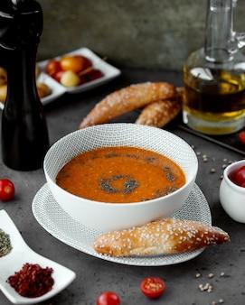 挽いた胡pepperをまぶした白いボウルにレンズ豆のスープ