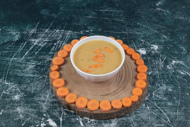 Чечевичный суп в белой миске и ломтики моркови. фото высокого качества