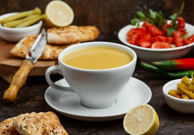 Lentil soup served in cup with lemon