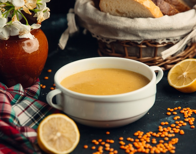 Lentil soup served in white bowl with lemons and bread