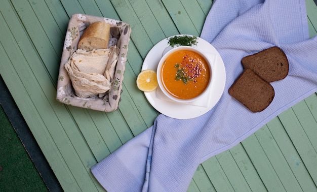 Lentil soup served with lemon and bread slices on a blue table