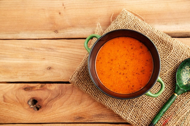 Lentil soup in a soup plate on a canvas on a wooden background. top view