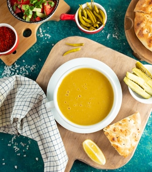 Lentil soup with bread on wooden board
