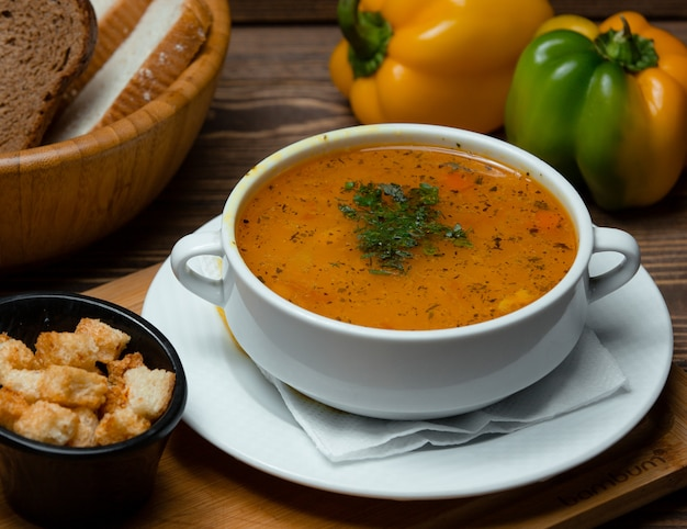 Суп из чечевицы с рубленой зеленью и крекерами.