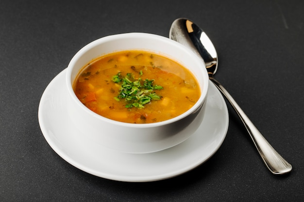 Lentil soup with mixed ingredients and herbs in a white bowl with a spoon.