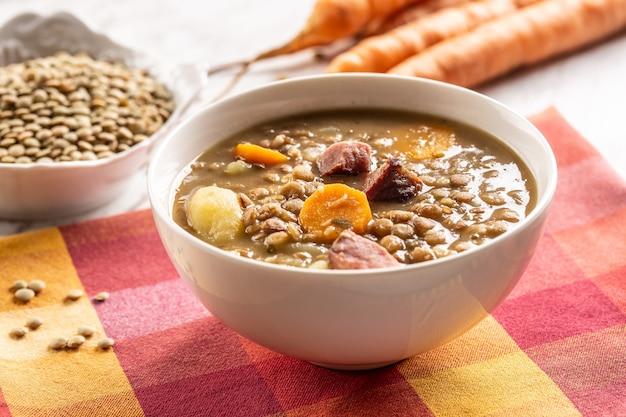 スモークポークネック、ニンジン、ジャガイモのレンズ豆のスープ。伝統的なスロバキア料理、チェコ料理、または東ヨーロッパ料理。